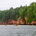 A group paddling toward the mainland sea caves.- Mainland Sea Caves from Meyers Beach
