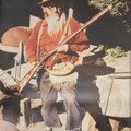 Buckskin Bill displaying some of his handmade goods in 1969: a helmet, a muzzle loader, a powder horn, and an amunition pouch.- Main Salmon River: Corn Creek to Carey Creek