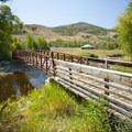 Pedestrian bridge over the Provo River at the Rock Cliff Nature Center.- Rock Cliff Nature Center + Interpretive Trail