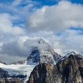 Mount Assiniboine summit visible above the clouds.- Nub Peak
