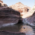 The first waterfall (with no flow) and a watering hole. The trail continues behind and up to the left from here.- Red Cliffs Nature Trail