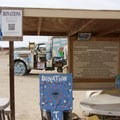 Informational signs and a donation box next to the entrance.- Salvation Mountain