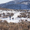 A skier pulling his kid on a sled while cross-country skiing.- Round Valley Trails, Quinn's Trailhead