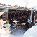 Picnic table, wood stove and wood piles in the Westview Shelter.- Westview Shelter