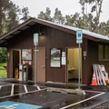 Restrooms and payment station at Nāmakanipaio Campground.- Nāmakanipaio Campground + Cabins