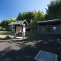 Entry signage and firewood storage at Dairy Creek Camp West.- Dairy Creek Camp East + West
