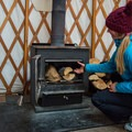 Fueling the stove to prepare for a cold night.- Arizona Nordic Village Cabins + Yurts