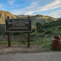 A sign marks the point when the trail leaves the road and descends into a lush canyon.- Escondido Falls
