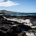 Narrow bands of sand lead between the lava rock at Kikaua Point.- Kikaua Point Park + Beach