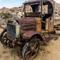 An ancient Mack truck sits with other historic vehicles.- Keys Ranch