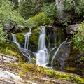 A set of waterfalls along the route.- Ptarmigan Tunnel Hike via Lake Elizabeth Foot Campground