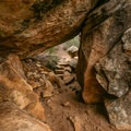 The trail cuts beneath boulders.- Lost Creek Canyon Falls