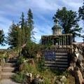 Vegetation encroaches on some sculptures at Petersen Rock Garden.- Petersen Rock Garden