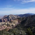 Views south along the Red Rock Escarpment. Mount Potosi, the southernmost of the Spring Mountain peaks, sits on the horizon, and Mount Wilson, the crown jewel of Red Rock, sits to the upper left. - Bridge Mountain