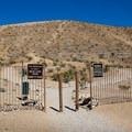 The peak trail lies behind an open gate.- Exploration Park Peak Trail