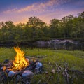 Campfire at sunset along the Manistee River.- Manistee River Trail Loop