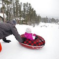 A man gives his daughter a push down the sledding hill at Carter Park. - Carter Park