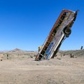 An old bus buried nose-first in the ground.- International Car Forest Of The Last Church