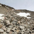A hiker navigating the scrambling section of the Mueller Hut route.- Mueller Hut Route