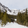 Wide open view of the gulch as two backcountry snowboarders make their way up the road.- McCullough Gulch