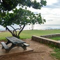 Picnic tables are situated with views of the ocean.- Lualualei Beach Park