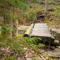 A small footbridge crosses a narrow side channel.- Grass River's Rainbow Falls