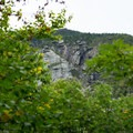 Massive cliff faces peek between the trees.- Sterling Pond