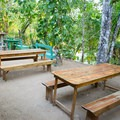 Restaurant seating next to the river at Clarissa Falls. - Clarissa Falls Resort