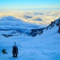The Reid Glacier and the summit shadow stretching across the clouds.- Mount Hood: Leuthold Couloir