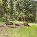 Hobo Camp features picnic tables and a barbecue pit.- Hobo Camp
