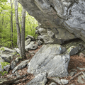 The path leads under outcroppings.- Chatfield Trail
