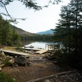 Hikers enjoy the dock at Lonesome Lake.- Lonesome Lake via Basin Cascade + Cascade Brook Trails