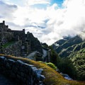 As sunset nears on the second day, the ruins of Sayacmarca greet visitors coming out of the clouds.- Machu Picchu via the Inca Trail