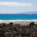 Blackish/brown basalt and white coral beach with Kaho'olawe in the distance.- Hoapili Trail / King's Highway