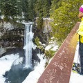 A snowshoer looks down at Brandywine Falls.- Brandywine Falls Snowshoe