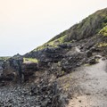 The trail is an unpaved four-wheel drive road that is washed out in many places.- Ka'ena Point Trail