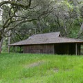 A wide closed building marks the point where the foot trail leaves Hitchcock Canyon Road.- Fern Falls via Kahn Ranch