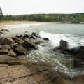 Waves crash along the rocky western edge of the beach.- Sand Beach