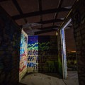 An ever-changing display of colorful graffiti covers an old pool and an adjacent building.- Two Guns Ghost Town