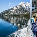 The Jenny Lake ferry boat cuts through the mirror-like surface of the water.- Jenny Lake Boat Tour
