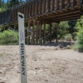 A marker signs where the trail leaves the riverside and climbs up the hillside.- Tahoe-Pyramid Bikeway: Farad to Floriston