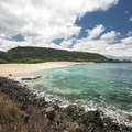 View of Waimea Bay Beach looking southwest with calm waters in the spring and summer.- Waimea Bay Beach Park