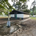 Public restroom and outdoor shower facilities at Kokololio Beach Park.- Kokololio Beach Park Campground