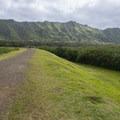 Hiking along the Nu'uanu Reservoir dam en route to Lulumahu Falls.- Lulumahu Falls Hike