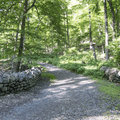 The trail crosses a bridge lined by rock walls.- Storm King Mountain