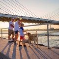 A family walks their dog along the south inlet beach.- Delaware Seashore State Park