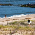 A surfer weighs his options at the dune crossing at the north inlet beach.- Delaware Seashore State Park