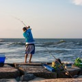 A man fishing into the Indian River Inlet.- Delaware Seashore State Park