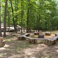 A fire pit and pavilion in the campground.- Big Hill Pond State Park