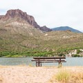 An isolated picnic table on a quiet spit of sand.- Apache Lake Campground + Marina